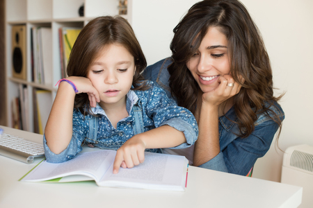 Foto de Mother helping her little child with homework - Imagen libre de derechos
