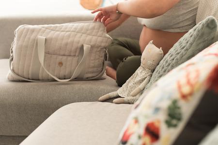 Photo pour Pregnant woman packing maternity bag for hospital labor - image libre de droit