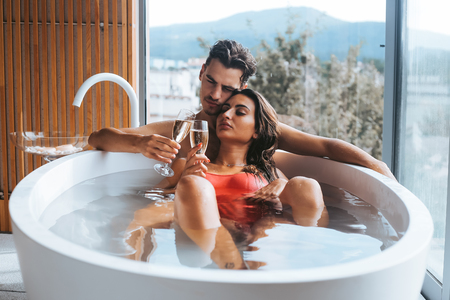 Foto de Beautiful couple enjoying a relaxing bath with champagne - Imagen libre de derechos