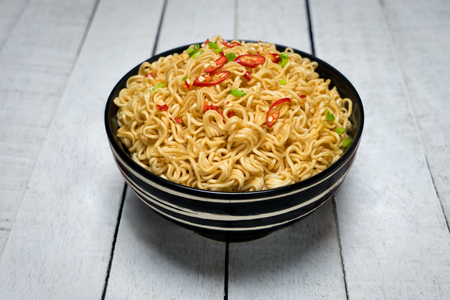 Instant noodles in the bowl on wooden background