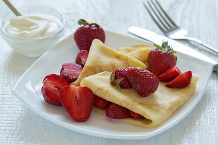 Foto de Pancakes with strawberries. On a white wooden background. Photo. - Imagen libre de derechos
