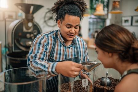 Foto de Bean roasting connoisseur allowing customer to smell the aroma from the coffee beans - Imagen libre de derechos