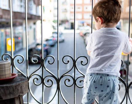 Foto de Boy looking out of the balcony in the quarantine. Good day. - Imagen libre de derechos
