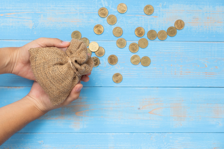 Foto de Woman hand holding money sack or bag with coins on blue wooden background. business, finance, retirement and money Saving for investment concept. - Imagen libre de derechos