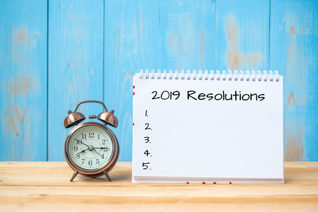 Photo pour 2019 Resolutions text on notebook and retro alarm clock  on table and copy space. Goals, Mission and New Start Concept - image libre de droit