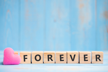 Photo pour FOREVER wooden cubes with pink heart shape decoration on blue table background and copy space for text. Love, Romantic and Happy Valentine's day holiday concept - image libre de droit