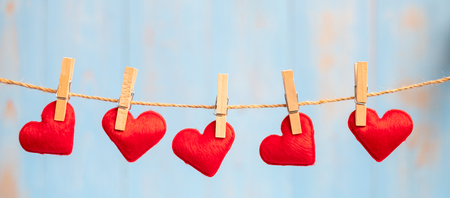 Photo pour Red heart shape decoration hanging on line with copy space for text on blue wooden background. Love, Wedding, Romantic and Happy Valentine' s day holiday concept - image libre de droit