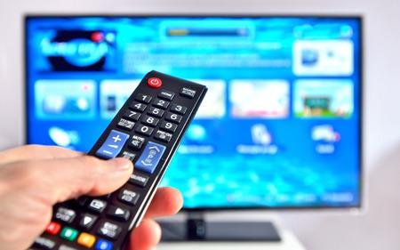 Foto de Smart tv and hand pressing remote control - Imagen libre de derechos