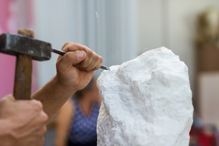Foto de Young student at work learning craftsman profession in art class, working with hammer to carving stone statue from white stone - Imagen libre de derechos