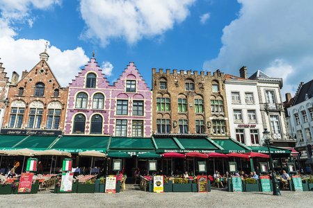 Foto de Bruges, Belgium - August 31, 2017: Old colorful traditional houses with bars and restaurants in the Grote Markt ( Market Square ) with people around in the historic center of the medieval city of Bruges, Belgium - Imagen libre de derechos