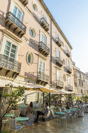 Foto de Siracusa, Italy - August 17, 2017: Terrace of a restaurant bar with people around on a street in the old town of the historic city of Siracusa in Sicily, Italy - Imagen libre de derechos