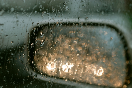 Droplets and car lights reflections on rear view mirror
