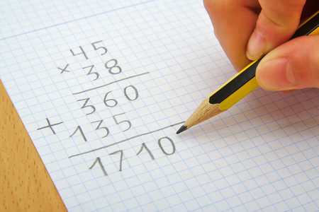 Photo for Hand of a child making a multiplication with a pencil. Math. School concept - Royalty Free Image