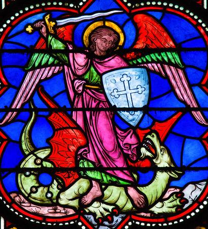 Foto de Stained glass window depicting Saint Michael the Archangel slaying Satan as a dragon, in Bayeux, Calvados, France. - Imagen libre de derechos