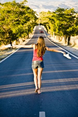 Young barefeet woman balancing in the middle of the road