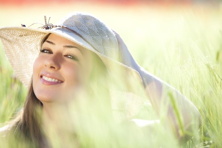 Young beautiful girl with hat staring at camera among green wheat, focus on the right eye.