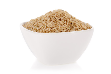 Foto de Brown rice in a bowl isolated on a white  - Imagen libre de derechos