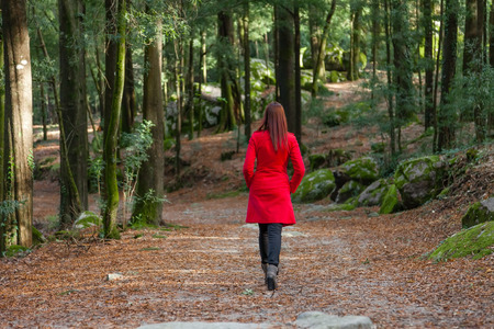 Photo pour Young woman walking away alone on a forest path wearing a red overcoat - image libre de droit