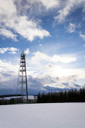 Foto de Snowy winter country with transmitters and aerials on telecommunication tower  - Imagen libre de derechos