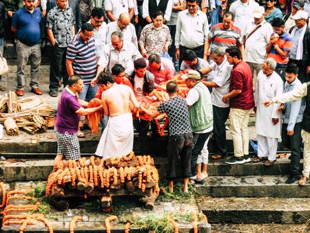 Photo for Kathmandu Nepal August 27, 2018 Hindu people attending a religious ceremony, the cremation of a dead body front the river at the Pashupatinath temple in the afternoon - Royalty Free Image