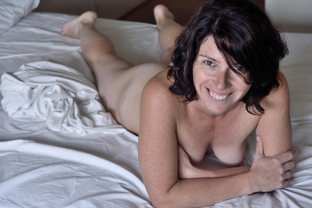 Foto de portrait of a smiling woman on the  bed - Imagen libre de derechos