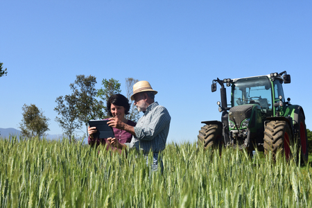Photo pour couple of farmers in a field with a digital tablet - image libre de droit