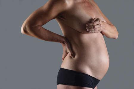 Foto de torso of pregnant woman on gray background - Imagen libre de derechos