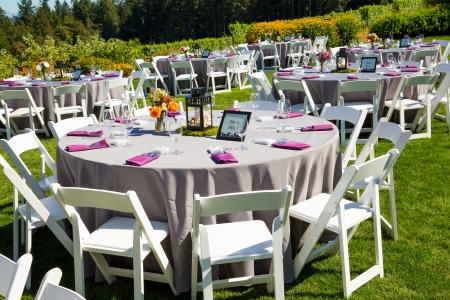 Foto de Tables, chairs, decor, and decorations at a wedding reception at an outdoor venue vineyard winery in oregon. - Imagen libre de derechos