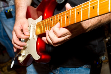 Talented musician plays the guitar during a solo.