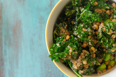 Foto de Superfood salad with raw kale, quinoa, blueberries, and barley is perfect for the paleo diet for weight loss. - Imagen libre de derechos