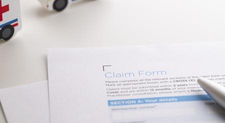 Photo pour Insurance claim form with pen and mini model car - image libre de droit