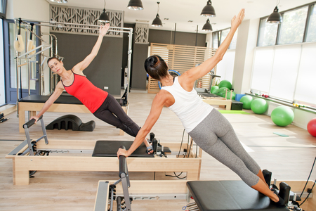 Photo pour Two girls are exercising pilates using pilates device reformer - image libre de droit