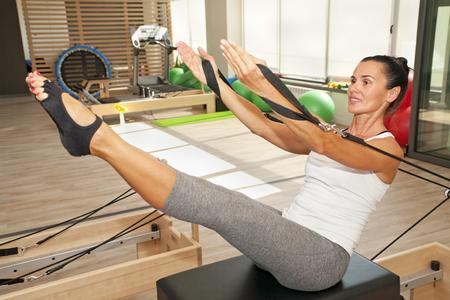 Photo pour Girl is exercising pilates using pilates device reformer - image libre de droit