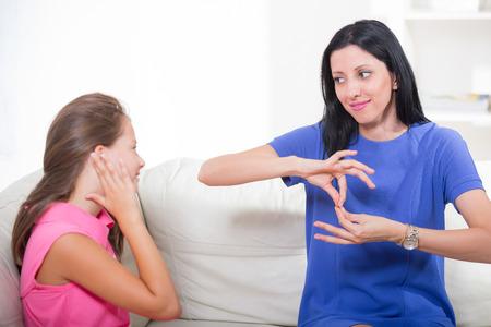 Photo pour Smiling deaf girl learning sign language - image libre de droit