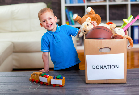 Photo pour Boy taking donation box full with stuff for donate - image libre de droit
