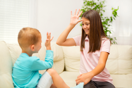Photo pour Brother and sister learn sign language at home - image libre de droit