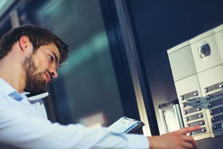 Foto de Portrait of a young happy businessman outside the office building enters the building - Imagen libre de derechos