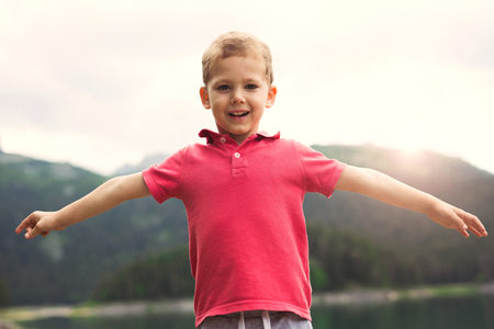 Foto de Little boy enjoying in the nature with arms wide open. - Imagen libre de derechos