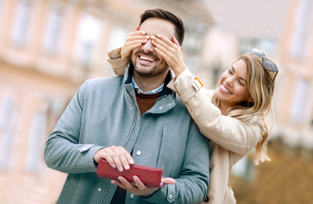Photo pour Woman surprising his boyfriend with a gift.Young woman with giftbox closing his boyfriend eyes to make a surprise for him. - image libre de droit