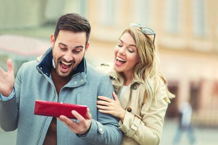 Foto de Woman surprising her boyfriend with a gift - Imagen libre de derechos