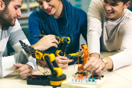 Photo pour Young students of robotics preparing robot for testing in workshop - image libre de droit