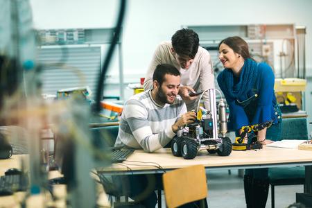 Foto de Young students of robotics preparing robot for testing in workshop - Imagen libre de derechos