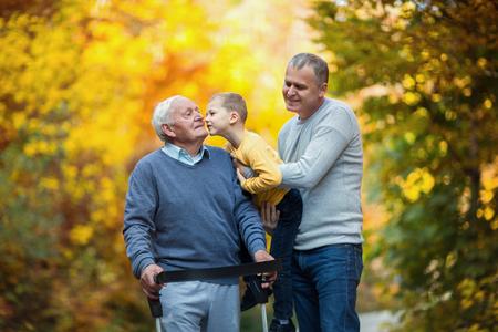 Foto de Elderly father adult son and grandson out for a walk in the park. - Imagen libre de derechos