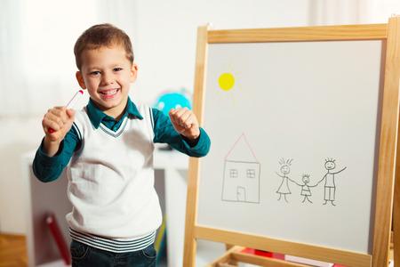 Foto de Cute little boy drawing on white board with felt pen and smiling. Early education concept - Imagen libre de derechos
