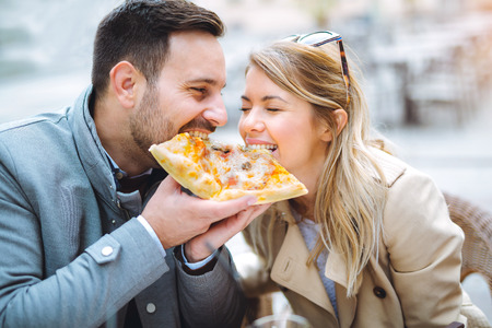 Foto de Couple eating pizza snack outdoors and smiling - Imagen libre de derechos
