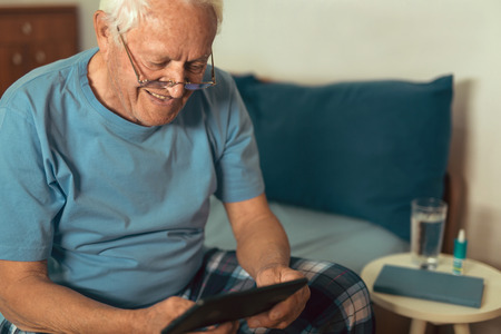 Photo pour Senior man using digital tablet. Surprised mature male using portable computer at home - image libre de droit