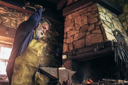 Foto de Senior blacksmith forge iron at work - Imagen libre de derechos