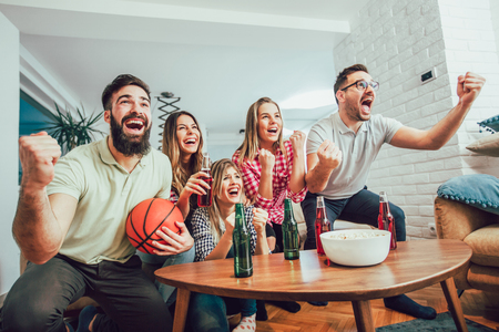 Foto de Happy friends or basketball fans watching basketball game on tv and celebrating victory at home.Friendship, sports and entertainment concept. - Imagen libre de derechos