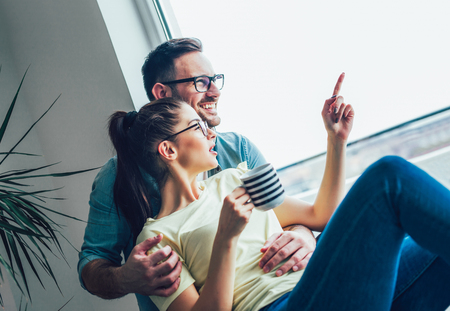 Photo for Image of young guy embracing his girlfriend and both looking through window - Royalty Free Image