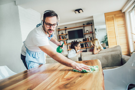 Photo for Husband housekeeping and cleaning concept. A man cleans the house, while women gossiping on the sofa - Royalty Free Image